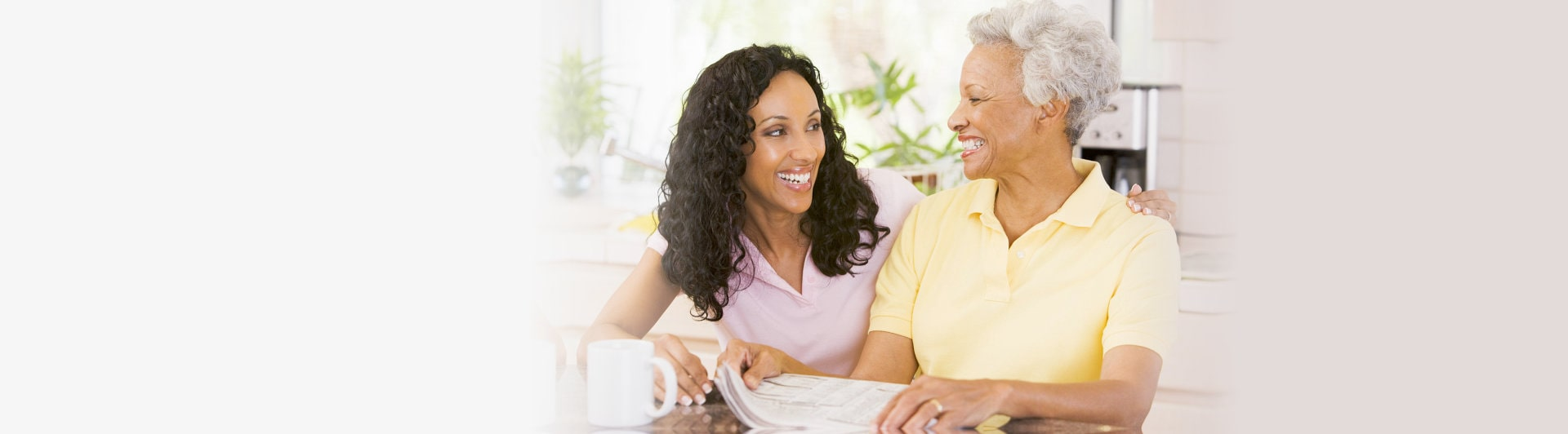 caregiver and elderwoman facing each other smiling