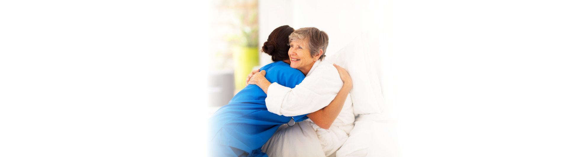 caregiver and elderwoman hug