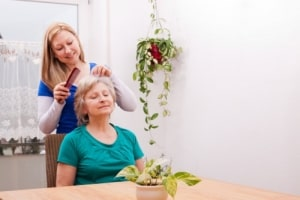 caregiver combing the hair of elderly woman